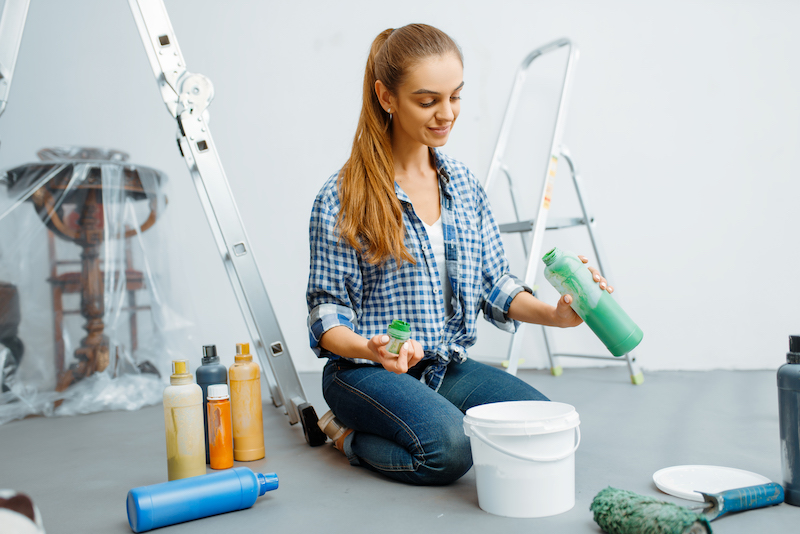 Female house painter mixes paints